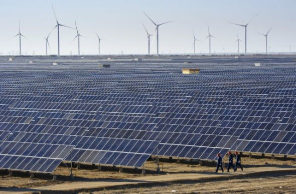 Workers walk past solar panels and wind turbines at a newly-built power plant in Hami